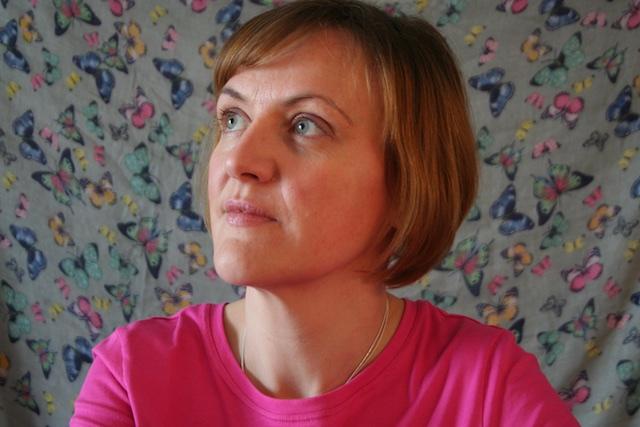 Selbstporträt von Doreen Trittel mit Schmetterlingen auf einem Tuch im Hintergrund