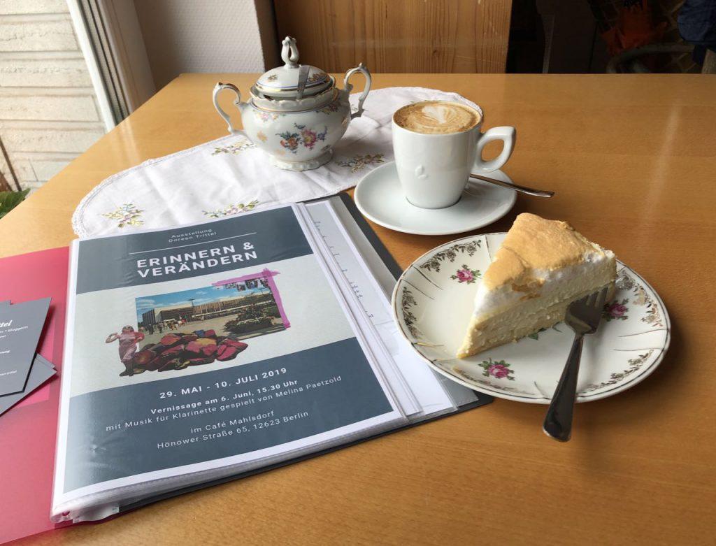 """Ausstellungsmappe """"erinnern & verändern"""" mit Cappuccino und einem Stück Kuchen im Café Mahlsdorf"""