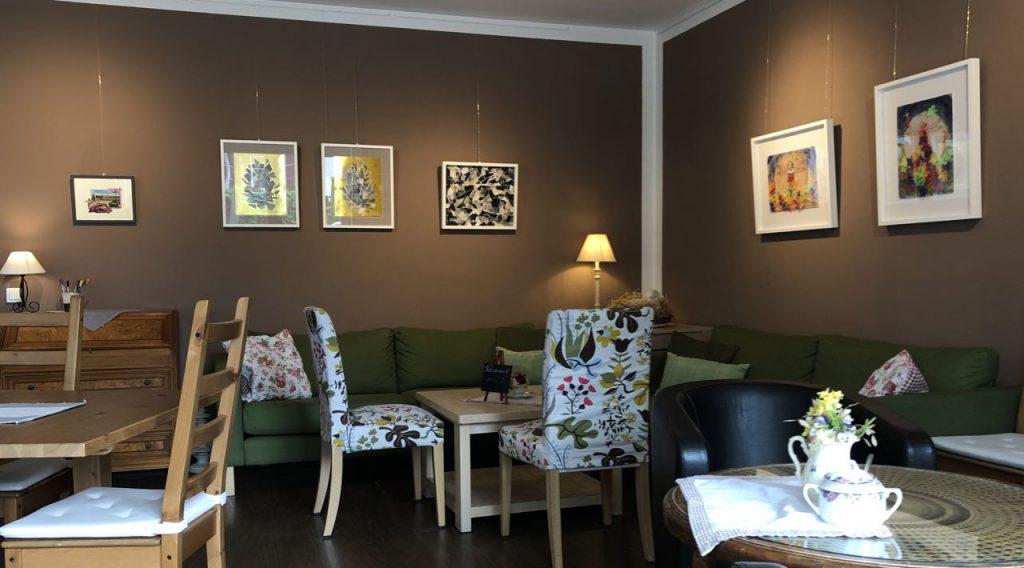 Ausschnitt vom Café Mahlsdorf, Sofaecke mit Bildern darüber von Doreen Trittel