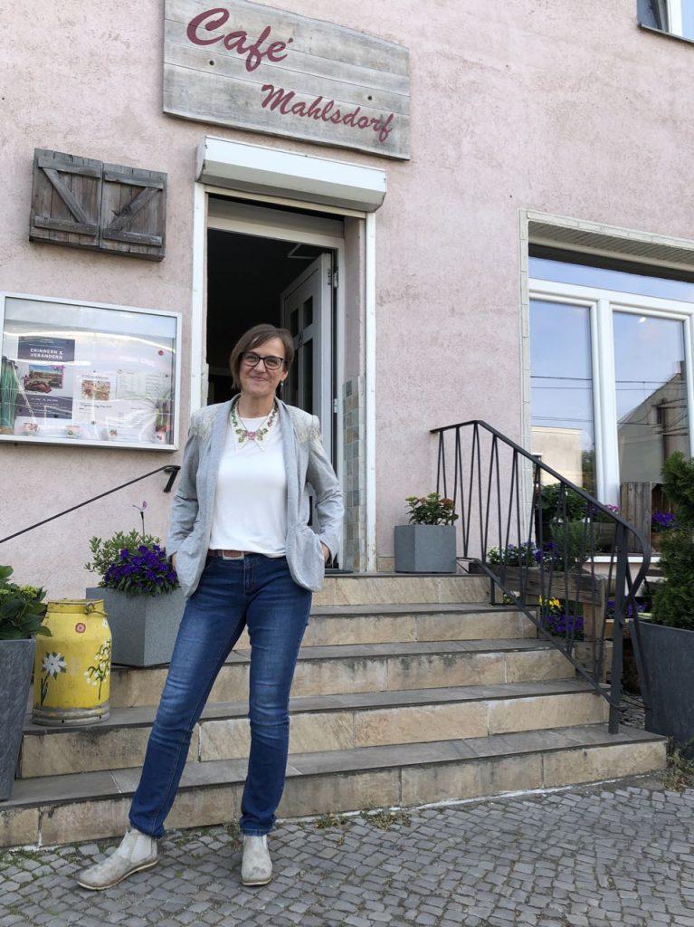 Die Künstlerin Doreen Trittel steht vorm Café Mahlsdorf mit ihrer Ausstellung, Collagen