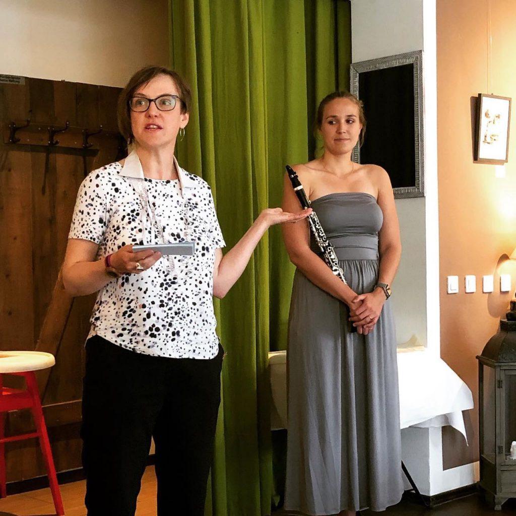 Doreen Trittel (links) hält eine Rede bei ihrer Vernissage. Daneben steht die Musikerin Melina Paetzold (rechts) mit ihrer Klarinette. Im Café Mahlsdorf, Hönower Str. 65, Berlin.