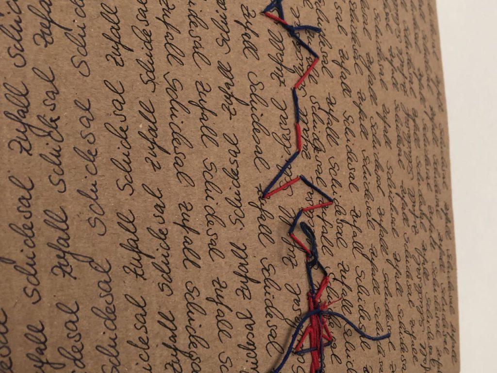 Schicksal Zufall abwechselnd auf Pappe, Rückseite, mit rotem und blauen Faden
